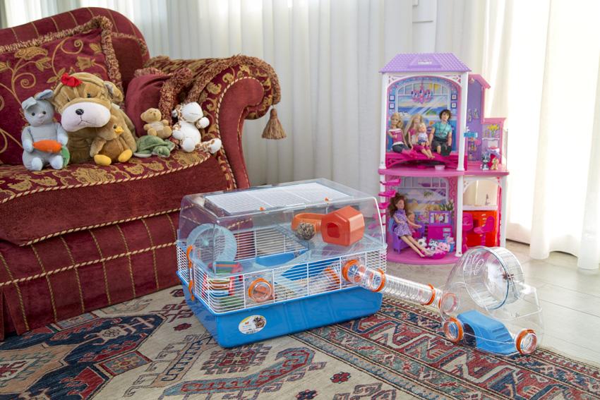 Gabbia per criceti Duna Fun di Ferplast in salotto con casa delle bambole e peluches