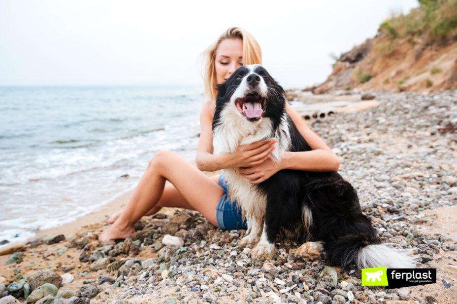 Mulher feliz abraçando o cachorro na praia