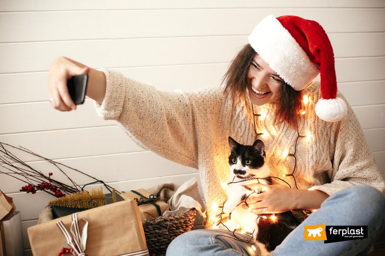 Счастливая стильная девушка с Санта шляпой селфи с милым котом