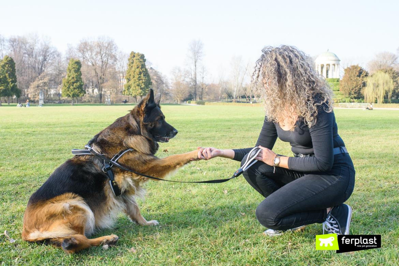 Proprietaria educa il cane singolarmente prima di portarlo a passeggio con guinzaglio Ferplast