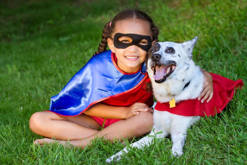 bambina-cane-supereroi-felici-prato